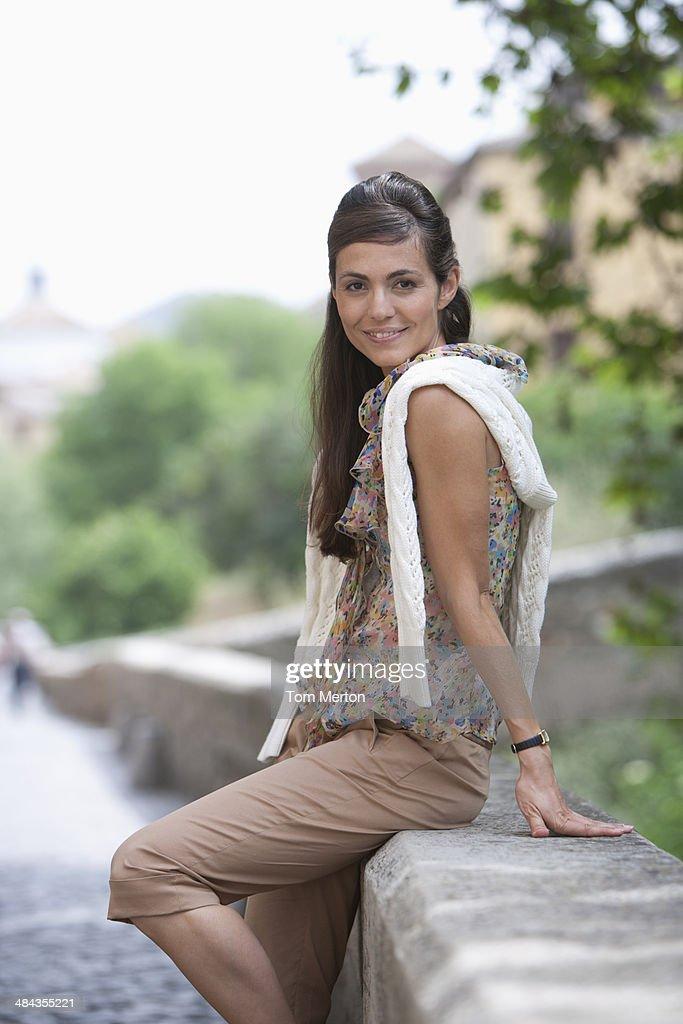 Woman sitting on wall  : Stock Photo