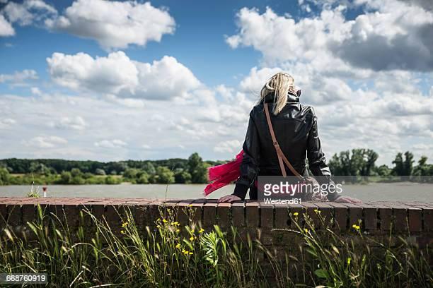 Woman sitting on wall, Rhine riverside