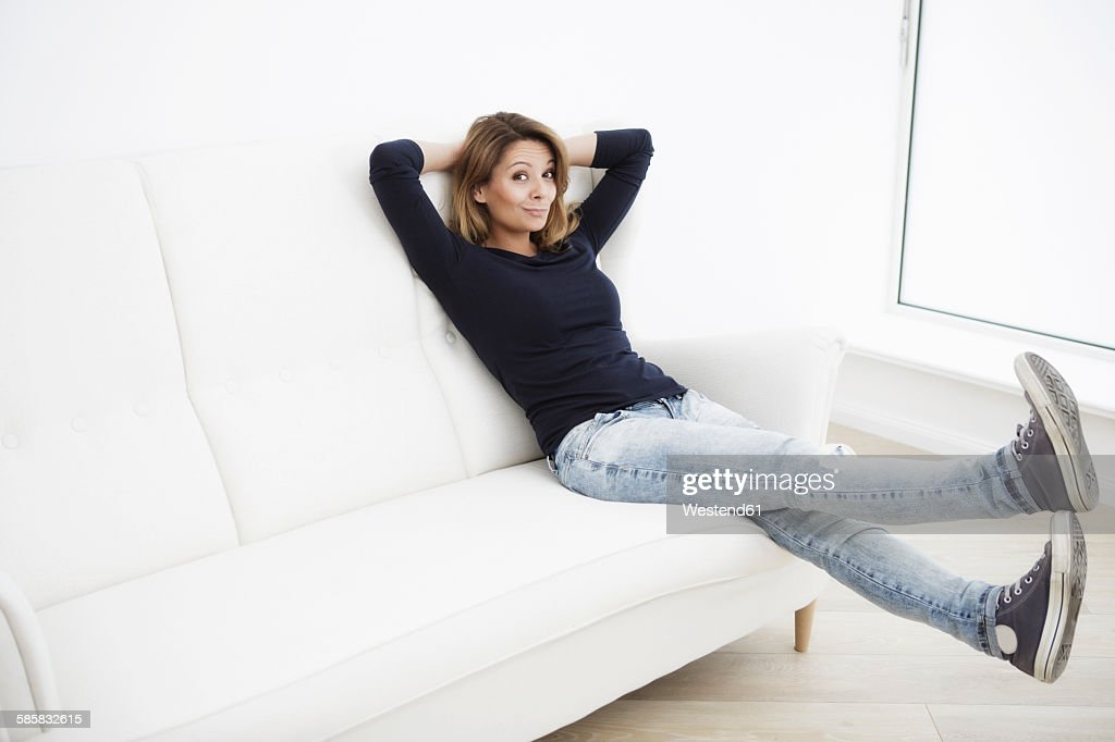 Woman sitting on white couch with legs in the air