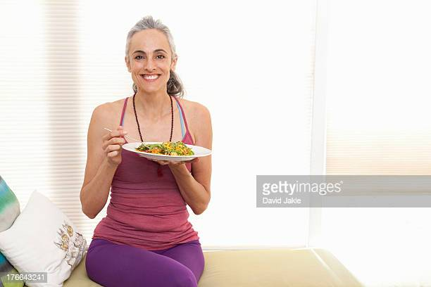 Woman sitting on window seat eating lunch, portrait