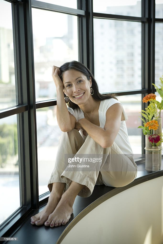 Woman Sitting On Window Sill At Home Portrait Stock Photo