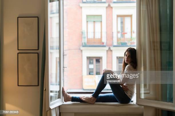 Woman sitting on window sill at open window