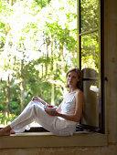 Woman sitting on window sill holding breakfast bowl, smiling, portrait