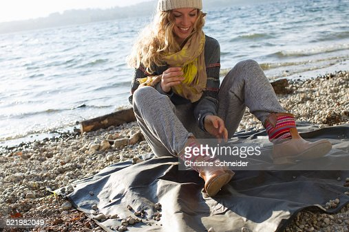 Woman sitting on windy beach