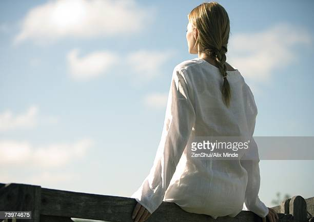 Woman sitting on wooden rail, facing sky