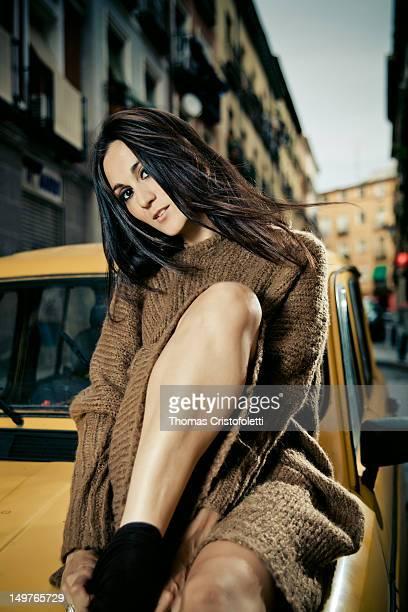 Woman sitting on yellow car