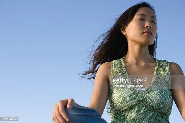 Woman sitting outdoors with eyes closed