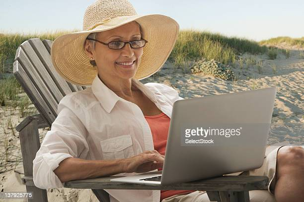 Woman sitting outdoors with laptop