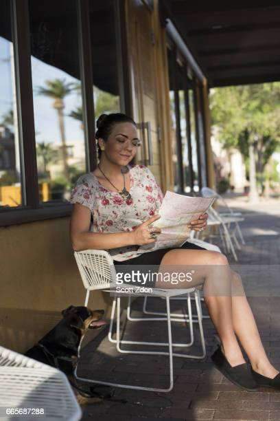 Woman sitting outside cafe holding map