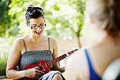 Woman sitting outside playing ukulele and singing