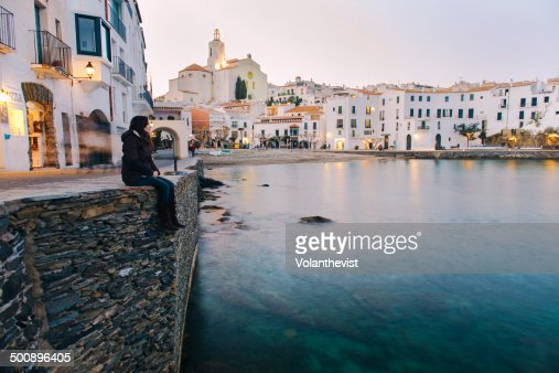 Woman sitting seaside in the Cadaqués at sunset