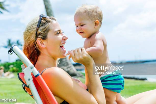 Woman sitting under palm tree with little son (18-23 months)