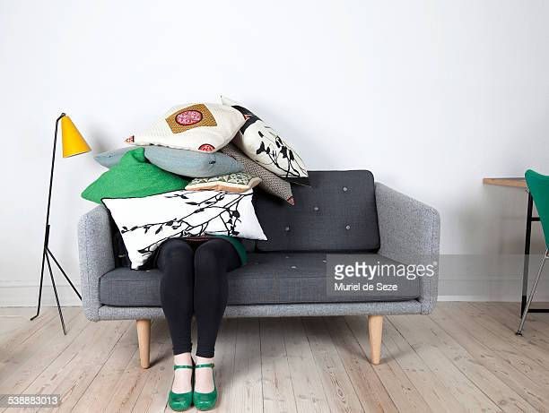 Woman sitting under pile of pillows