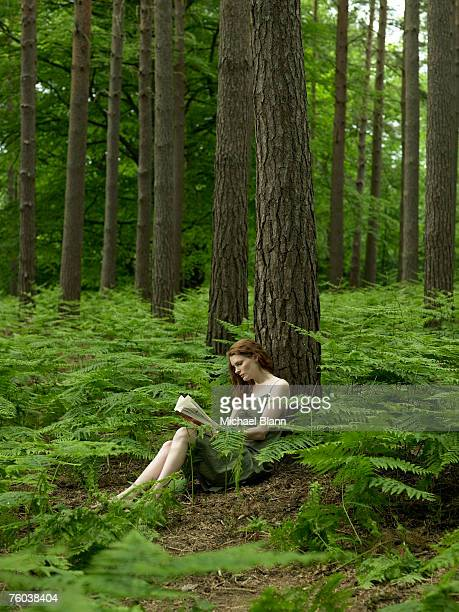 Woman sitting under tree in forest, reading book