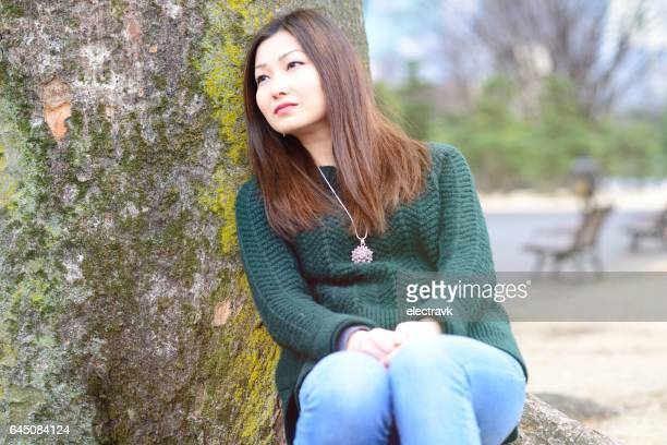 Woman sitting under tree