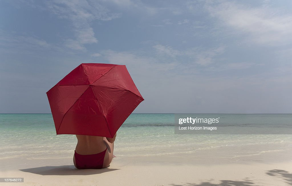 Woman sitting under umbrella on beach