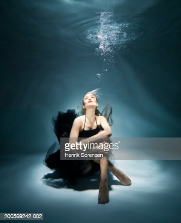 Woman sitting underwater, looking up : Stock Photo