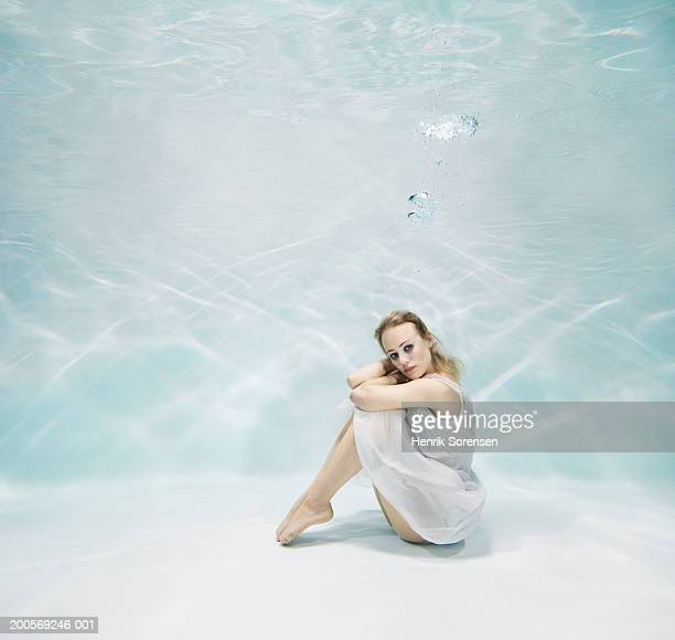 Woman sitting underwater, portrait, side view
