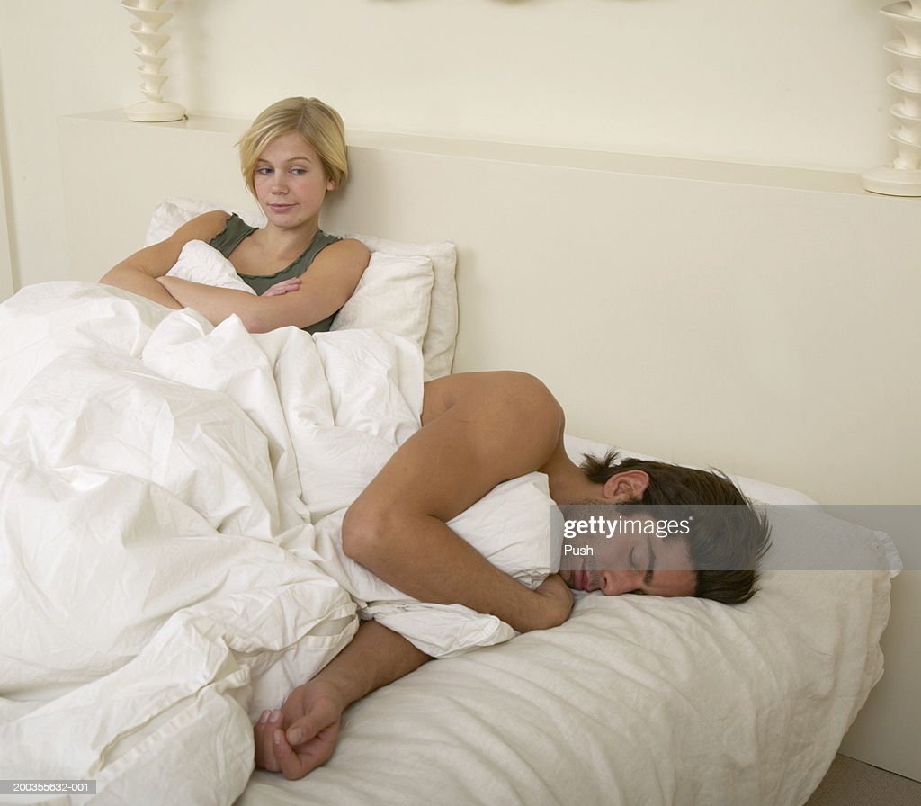 Woman sitting up in bed watching man sleeping arms folded for Beds that sit up