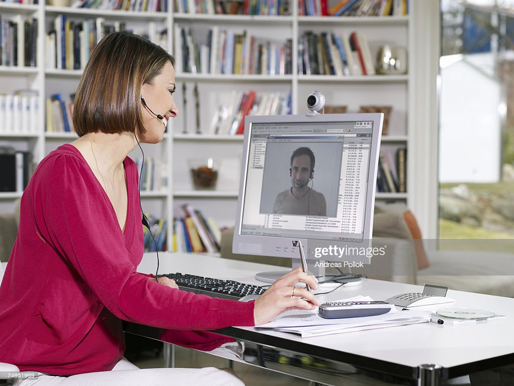 Woman Sitting Videoconferencing with Man on Computer : Stock Photo