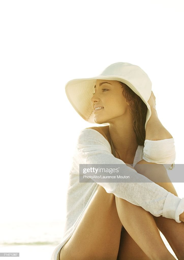 Woman sitting wearing sun hat, looking into distance