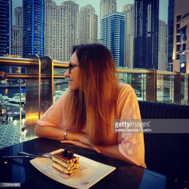 Woman Sitting With Cake At Restaurant