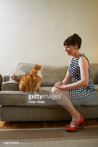 Woman sitting with cat on sofa : Stock Photo