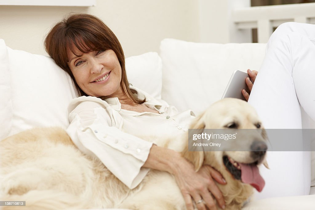 Woman sitting with dog on sofa using digital tablet : Stock Photo