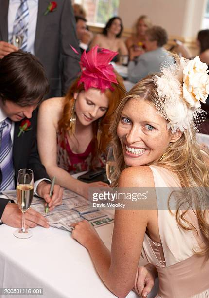 Woman sitting with friends at race day, smiling, portrait