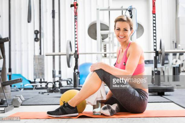 Woman sitting with heavy ball on exercise mat in gymnasium