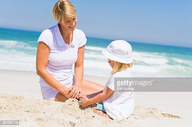 Woman sitting with her daughter on the beach
