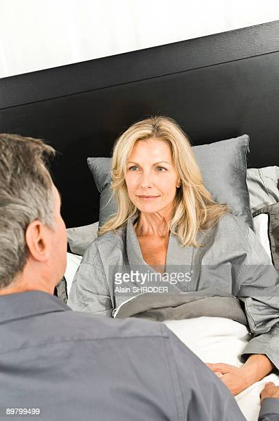Woman sitting with her husband on the bed