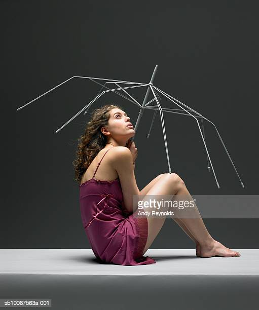 Woman sitting with holding umbrella frame, side view