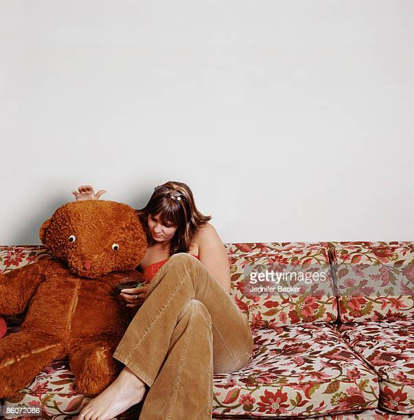 Woman sitting with large teddy bear