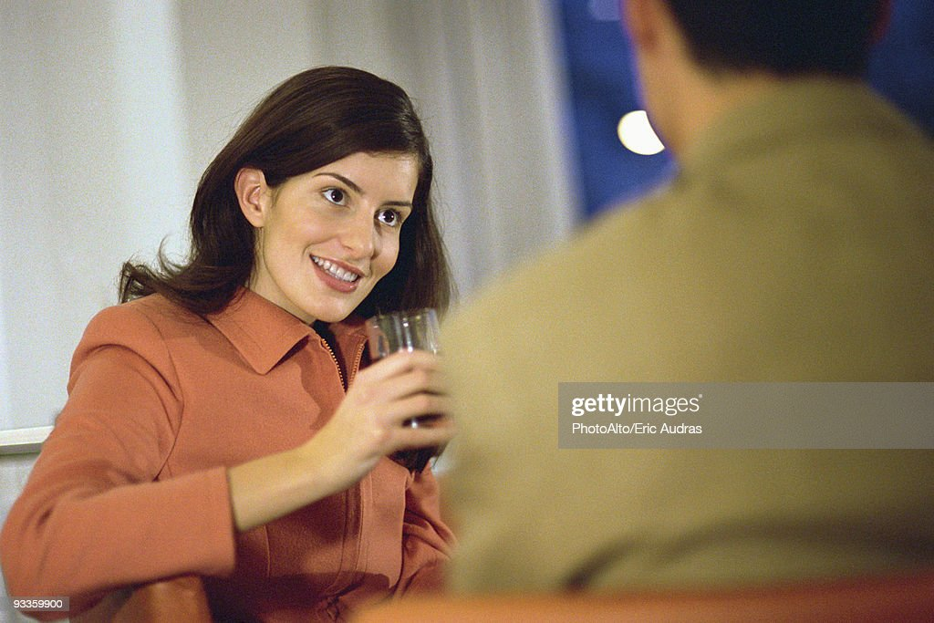 Woman sitting with man, holding glass of red wine : Stock Photo