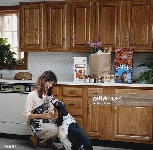 Woman sitting with pets in kitchen, smiling