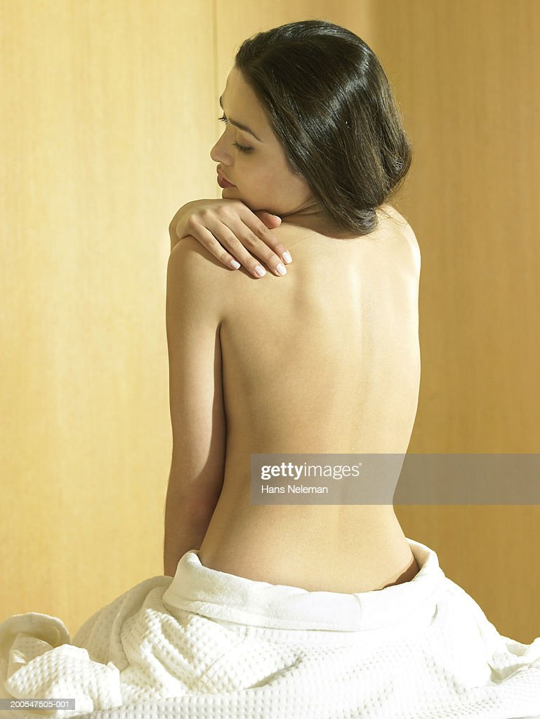 Woman sitting with towel, looking back over shoulders, rear view : Stock Photo