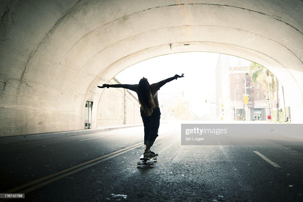 Woman skateboarding in tunnel