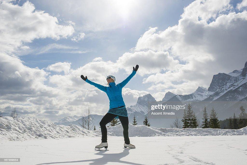 Woman skates on frozen pond under snowy mountains : Stock Photo
