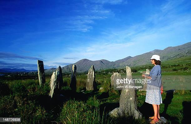 Woman sketching ancient stone circle.