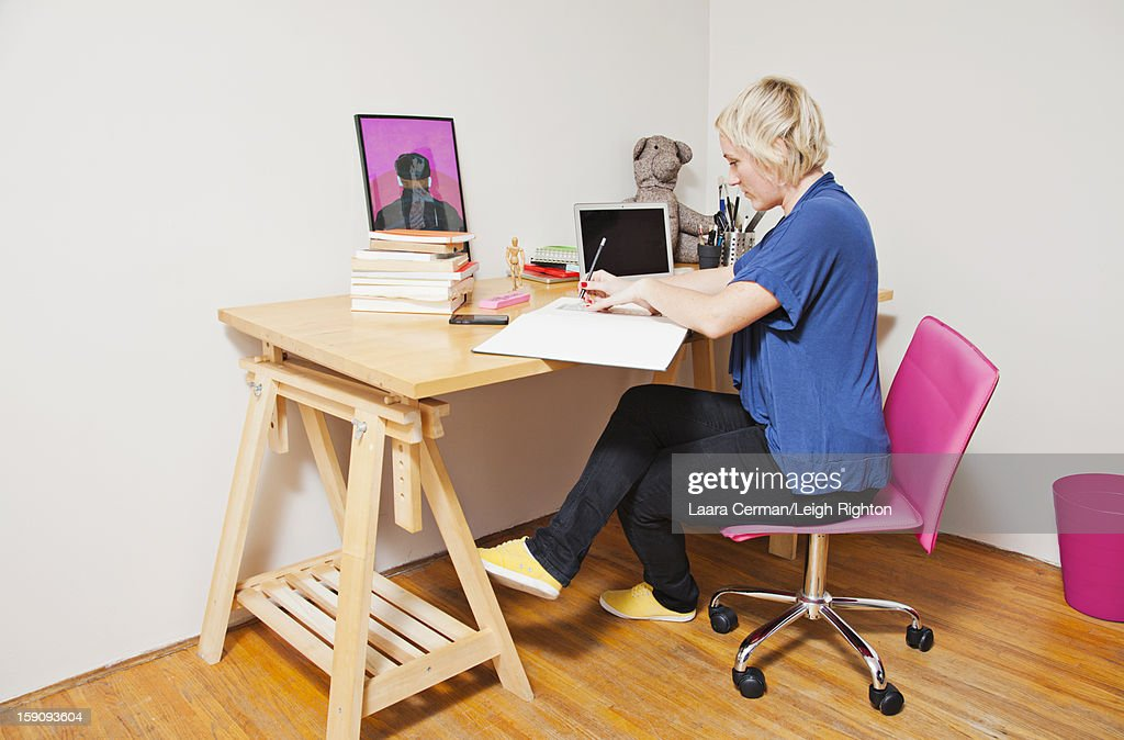 Woman sketching at desk in home office. : Stock Photo