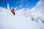 Woman skiing fresh powder on sunny day