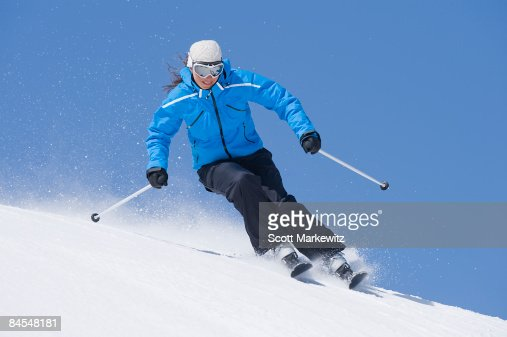 Woman skiing in blue jacket : Stock Photo