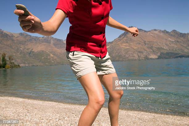 Woman skipping rocks on mountain lake