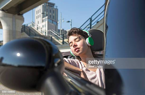 Woman sleeping and listening to music in open top car