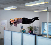 Woman sleeping floating above her office table.