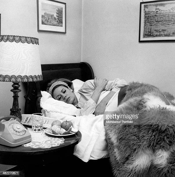A woman sleeping in a bed keeping herself warm with a plush blanket beside a telephone and some furits on a dish 1960s