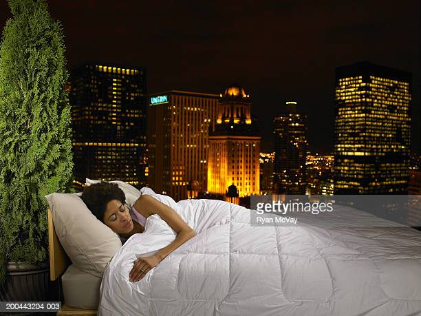 Woman sleeping in bed on rooftop of building