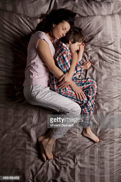 Woman sleeping in bed with her son