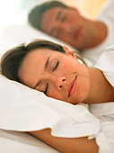 Woman sleeping in bed with man in background